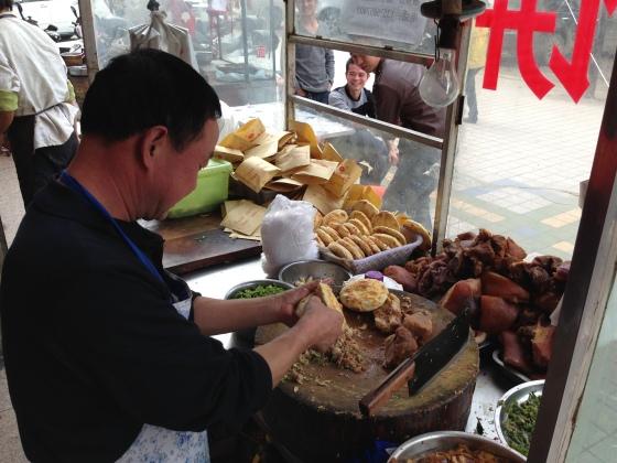 Rou Jia Mou... Pork + fat + raw garlic + crispy bun = the Shaanxi answer to the Big Mac (served while Matthieu tells a joke to chap in background) - in Lingbao, Henan