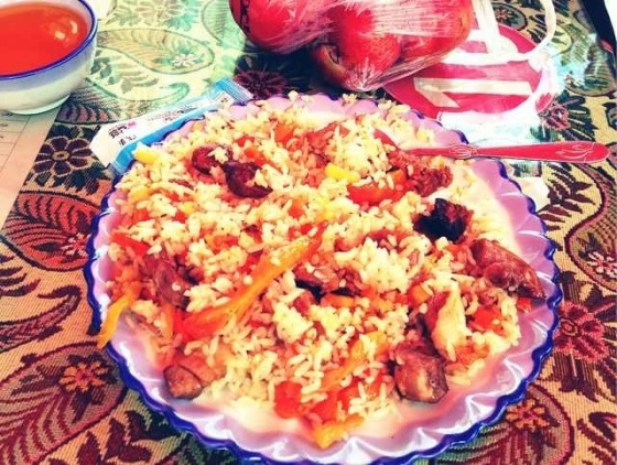 Fantastic dish of rice fried with sweetened carrot and chunks of mutton, the third most popular dish in all of Xinjiang behind mutton skewers and Lamian.  In Xinhe, Xinjiang Province, China.